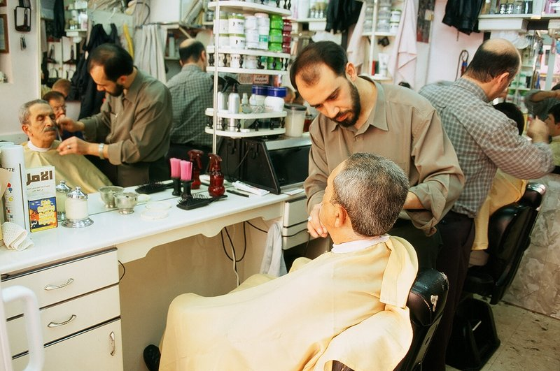two barbers cutting hair