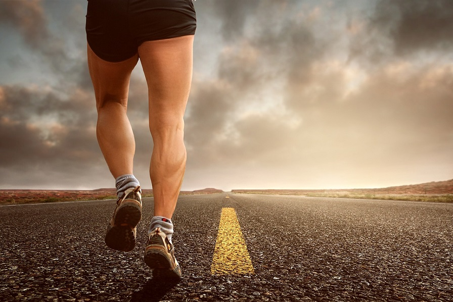 legs of man running on road