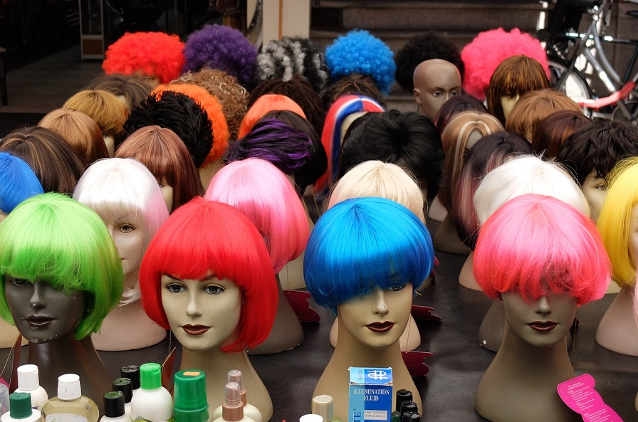 many heads of mannequins with different wigs