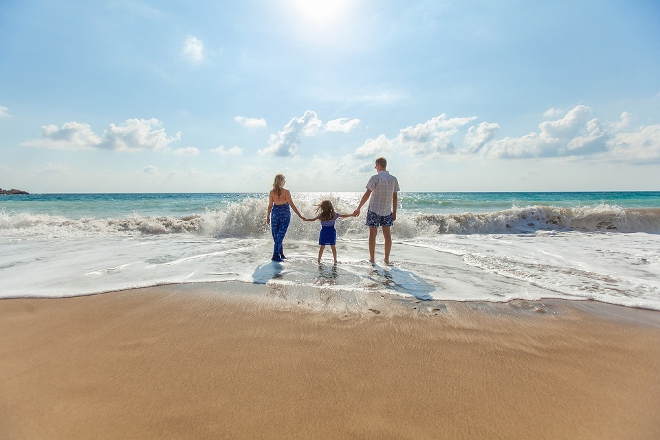 man, woman and child on the beach