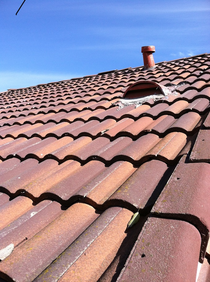 red tile roofing with vent and chimney